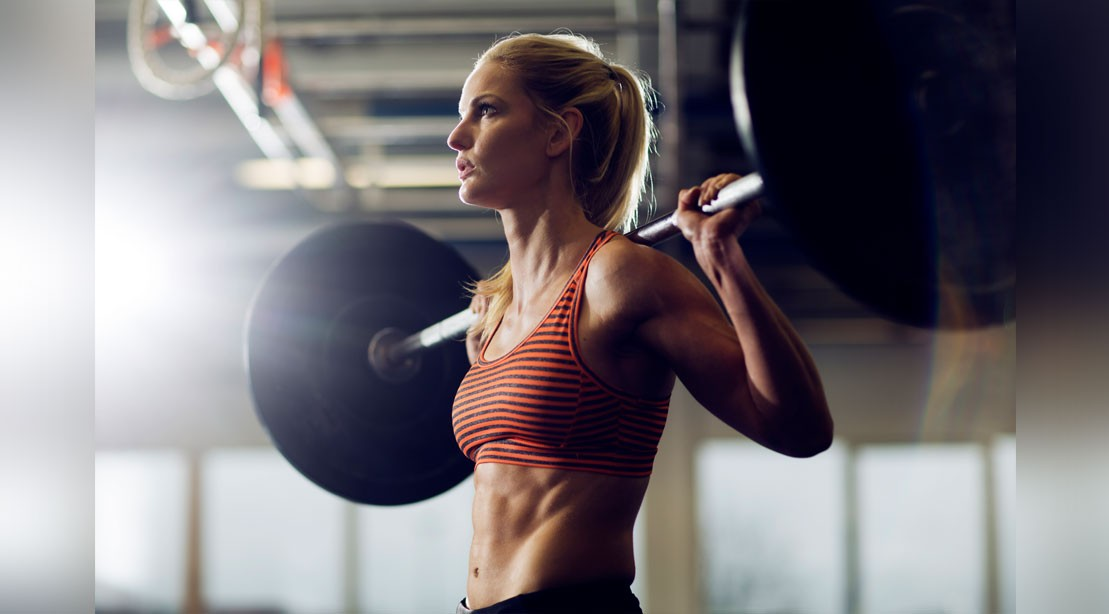 Fit woman with abs with barbell on shoulders