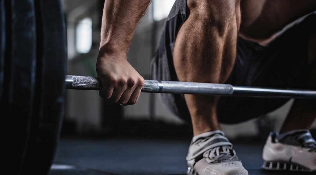 A photo of a person grabbing a barbell.