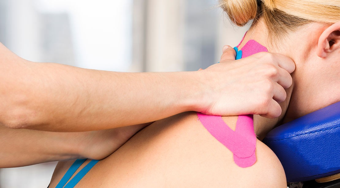 Kinesio tape being applied to a woman's neck.