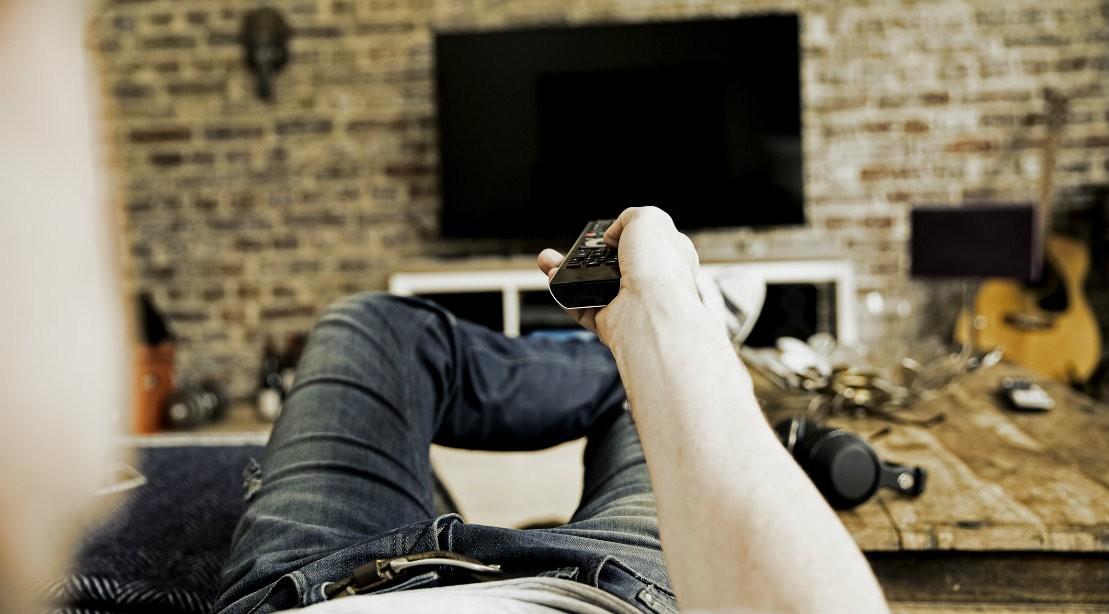 Man holding TV remote