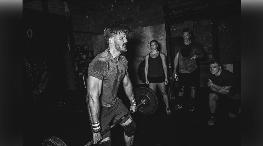CrossFitters watching man lift barbell