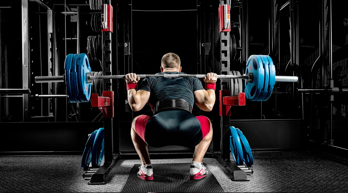 Powerlifter-In-Gear-Squatting-At-Power-Rack
