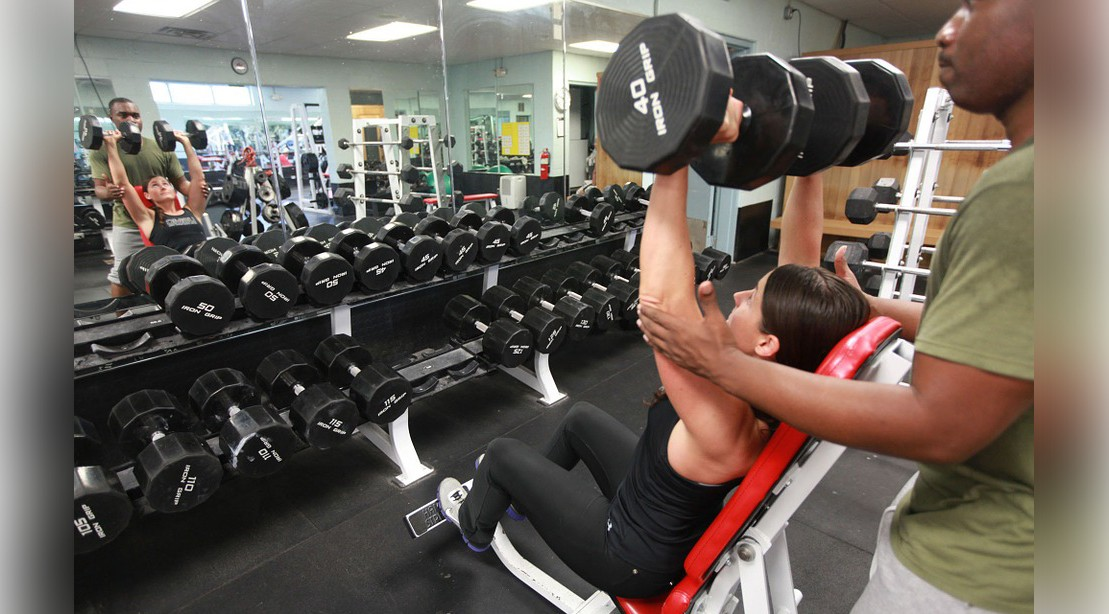 Woman Lifting Dumbbell Overhead At Gym