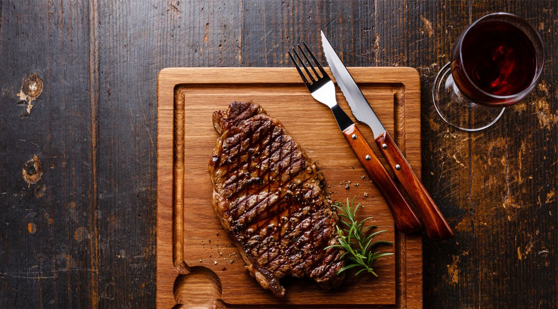Grilled Steak Striploin and red wine on cutting board