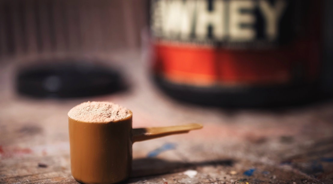 Protein powder in scoop on table