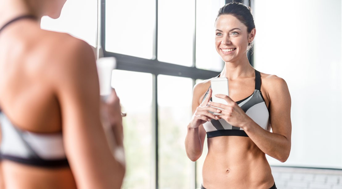 Fit woman taking selfie at gym