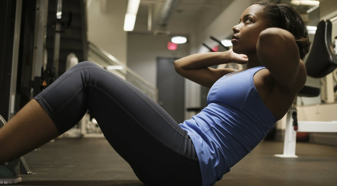 Woman performing situp in gym