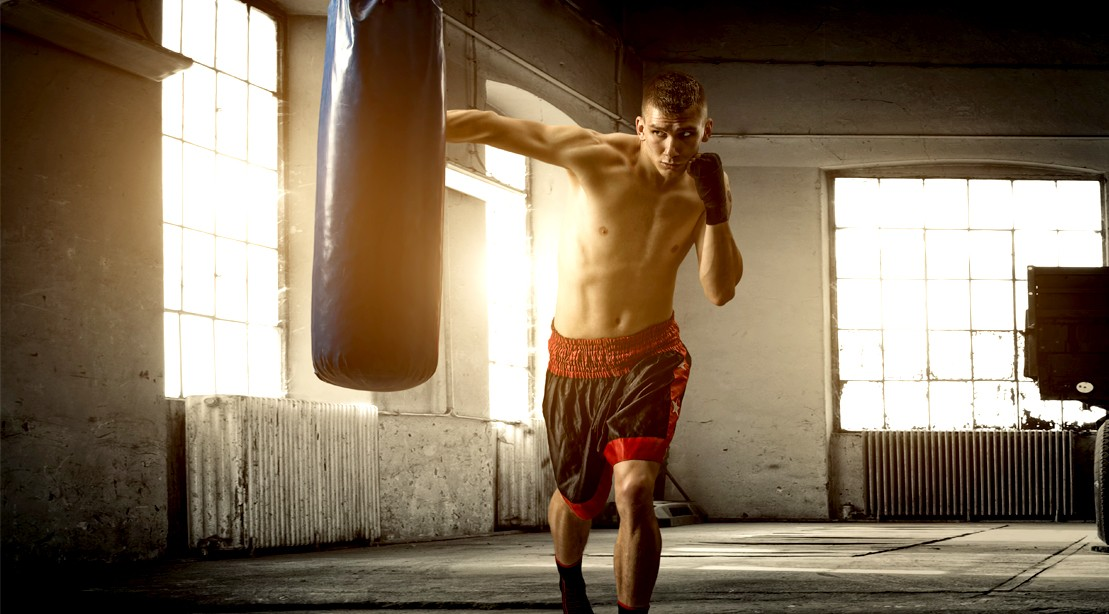 Young-Boxer-Punching-Heavy-Bag-In-Boxing-Gym
