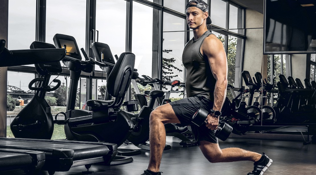 Young-Muscular-Man-Doing-Lunges-In-Dark-Gym