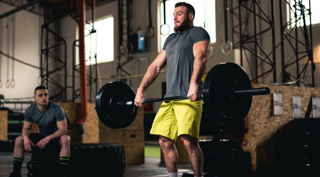 Man lifting heavy barbell at gym