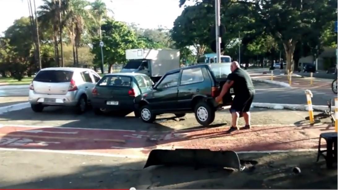 man lifts car
