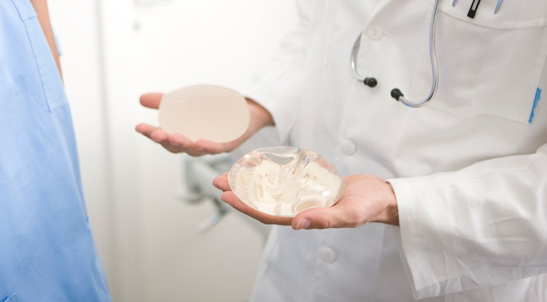 Doctor Holding Two Breast Implants