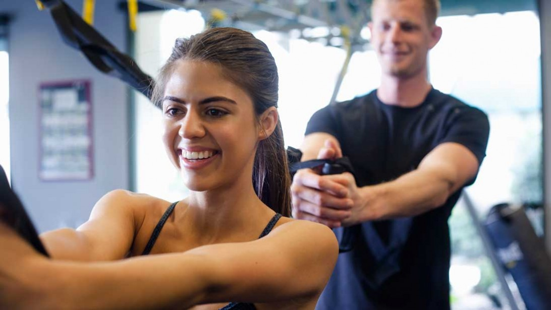 man and woman working out together at gym