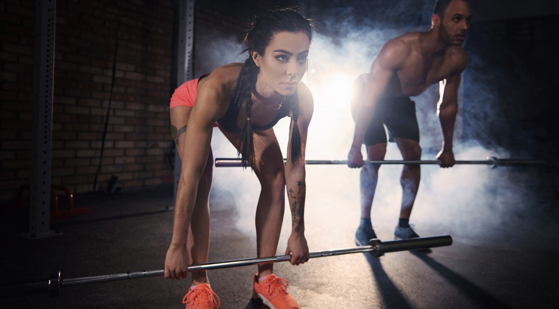 Couple Working Out With Barbells