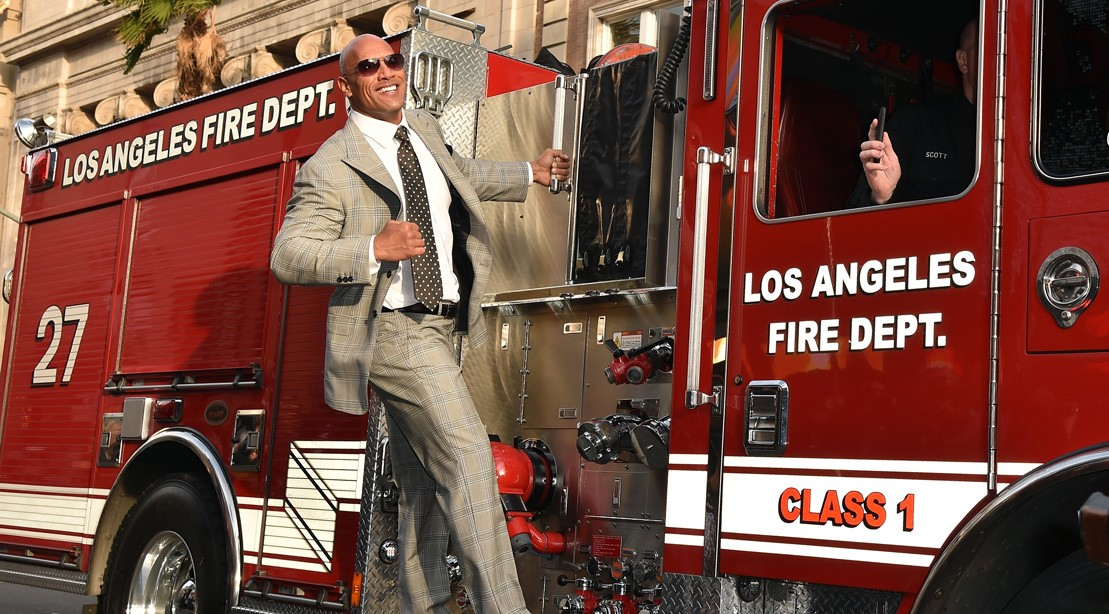Dwayne Johnson hangs off the side of a fire truck.