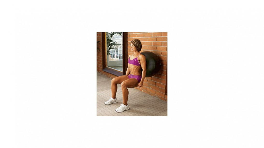 woman doing squat with exercise ball against a brick wall