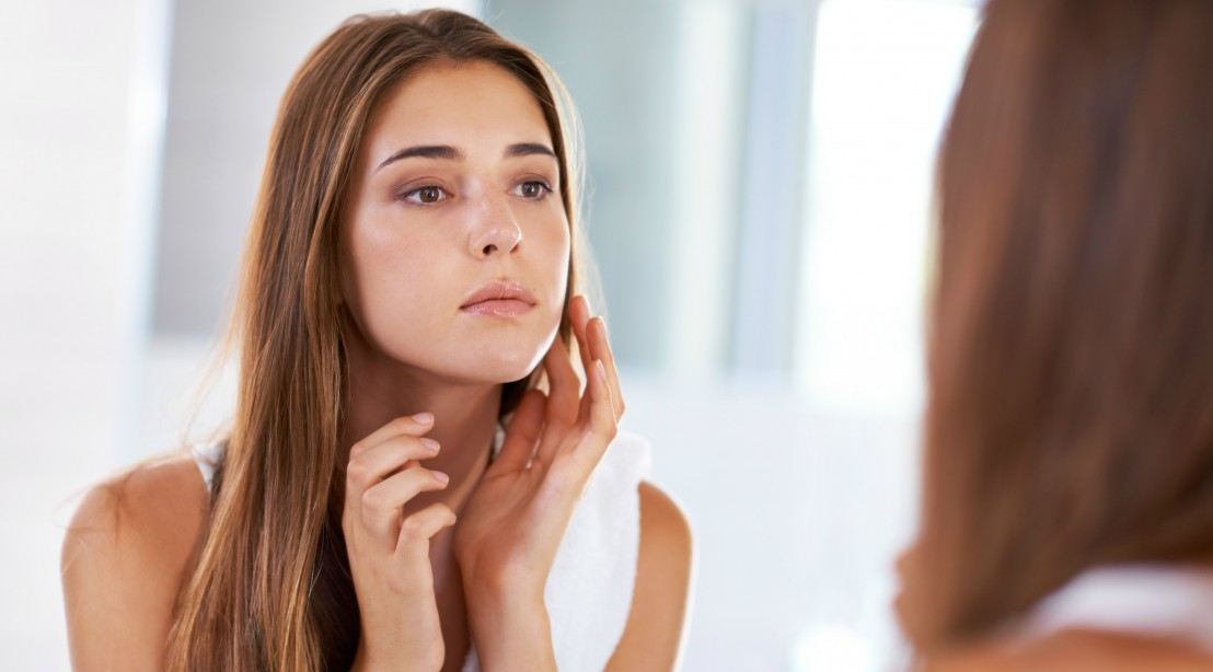 Woman With Youthful Skin Looking in the Mirror