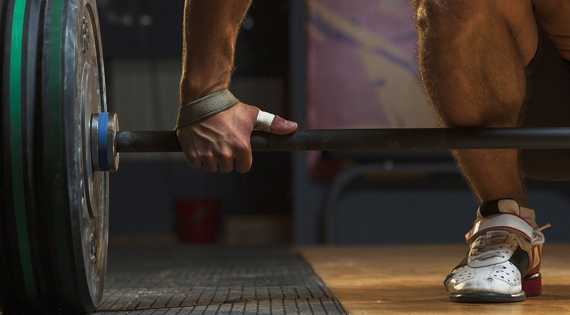 Man Holds Barbell Before He Does Weightlifting Exercise