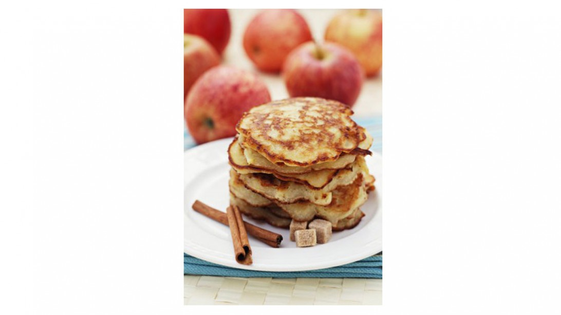 stack of harvest apple spice pancakes next to fresh whole apples