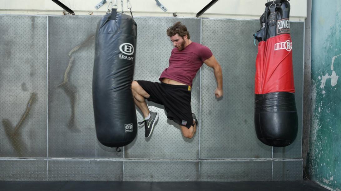 man throwing knee kick at heavy bag