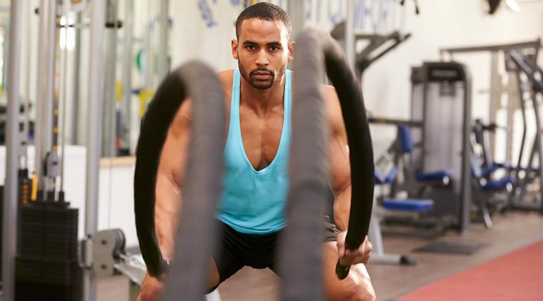 Man HIIT Training Battle Ropes At Gym