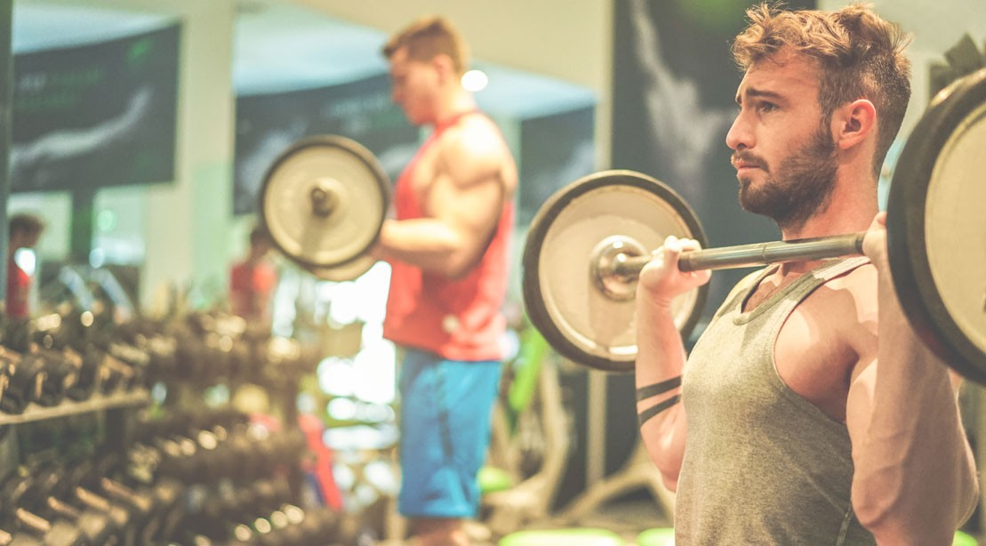 man tired in gym with barbell
