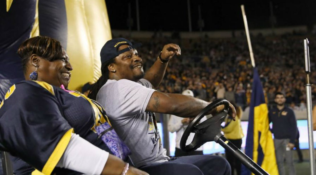 Marshawn Lynch drives a golf cart at a Call football game