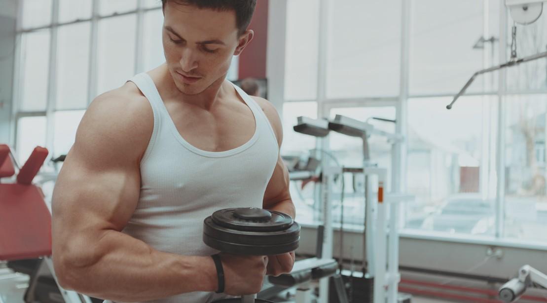Man Doing Biceps Curls in the Gym Focusing