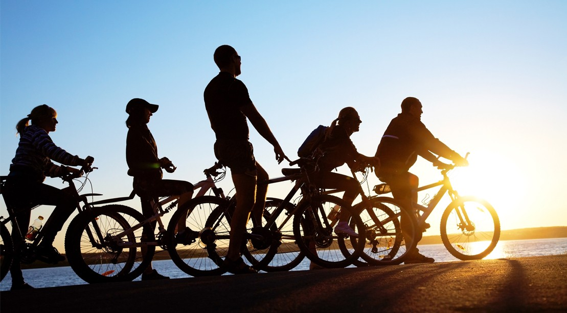 Active Men And Women Biking By The Water
