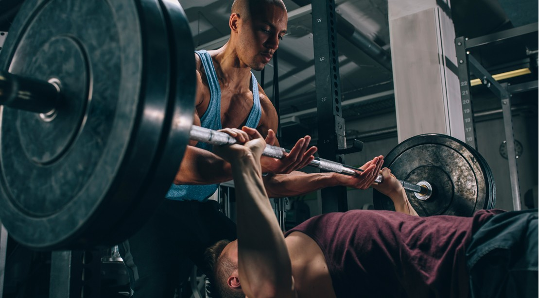 Man Bench Pressing With a Spotter