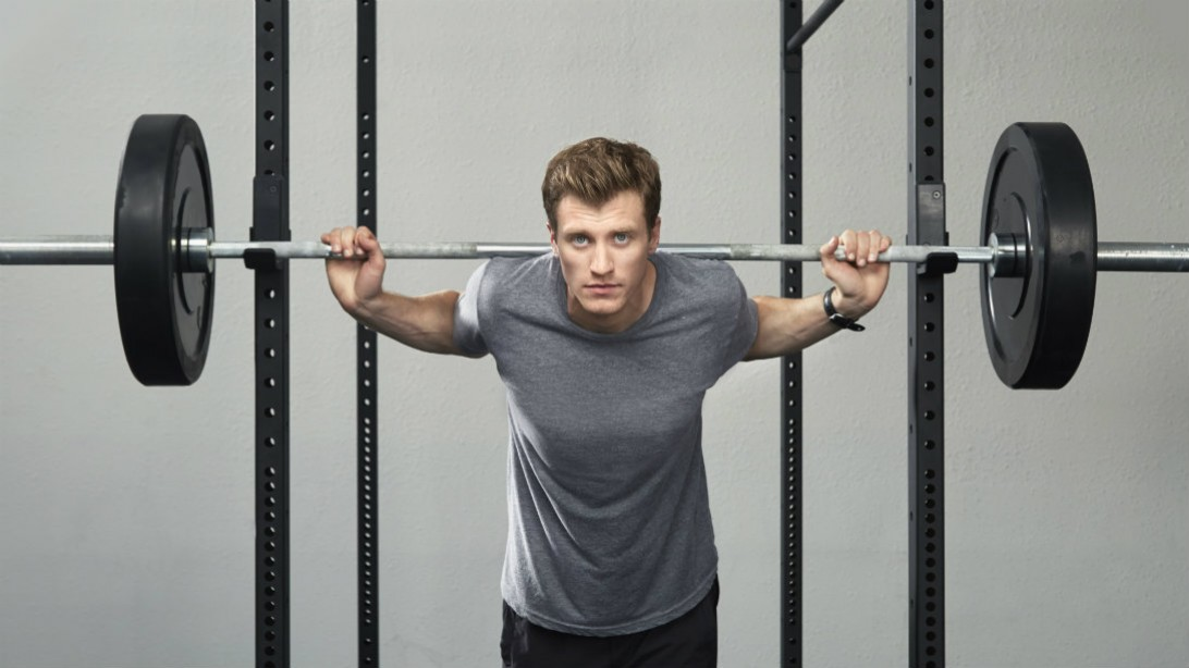 man standing at squat rack with barbell