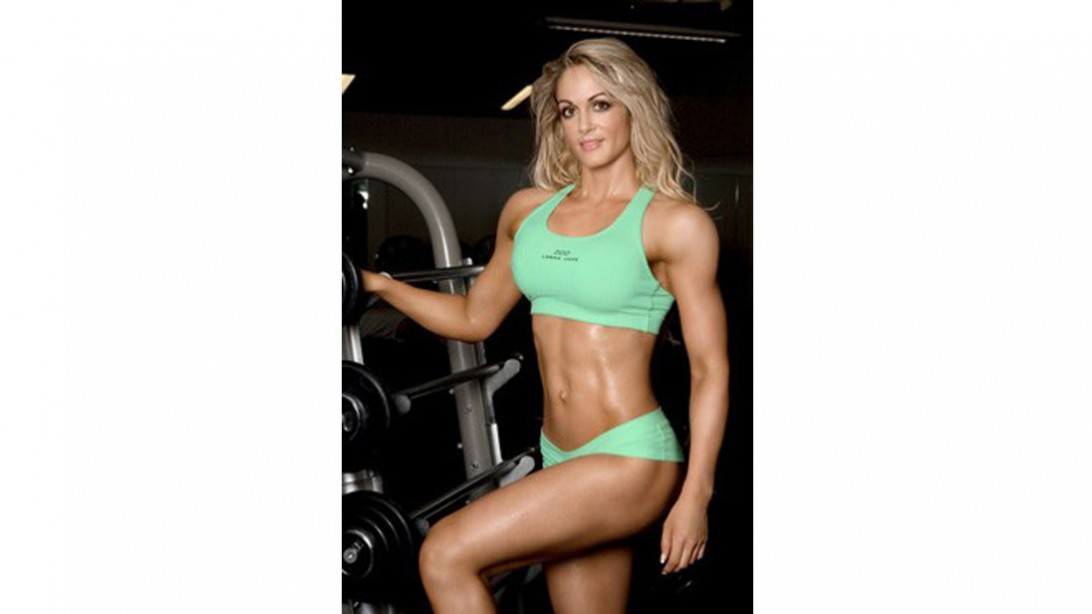 Raechelle Chase posing next to barbells in green outfit