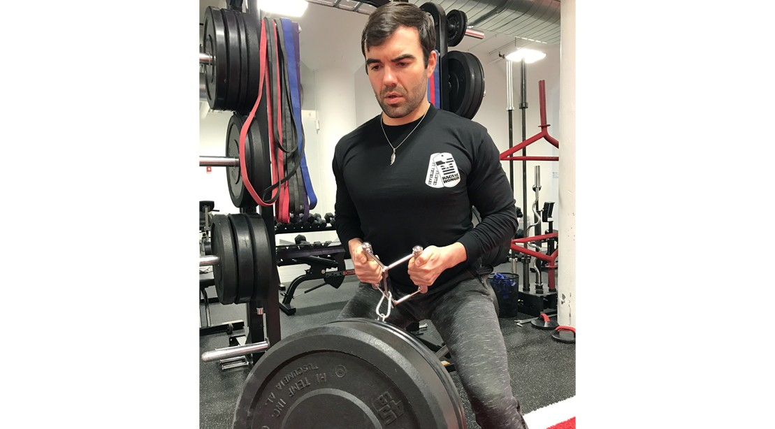 Man lifting weights in Rags of Honor t-shirt.