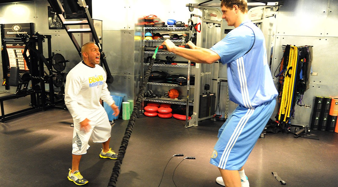 Strength and conditioning coach Steve Hess works with Timofey Mozgov #25 of the Denver Nuggets during the first day of training camp on December 9, 2011 at the Pepsi Center in Denver, Colorado.