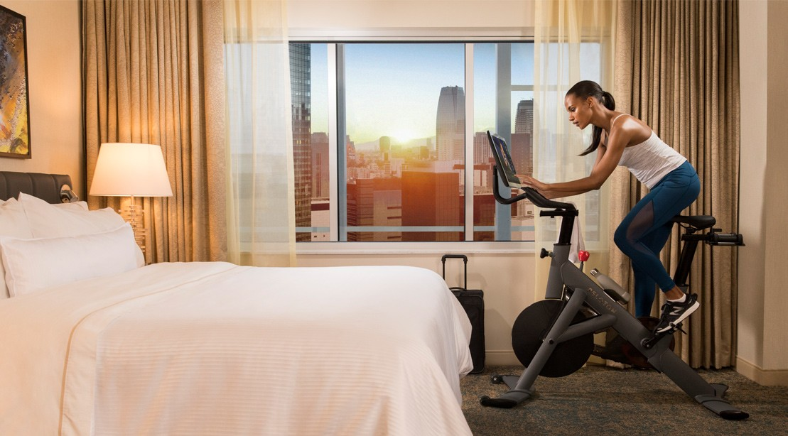Woman riding stationary bike in hotel room