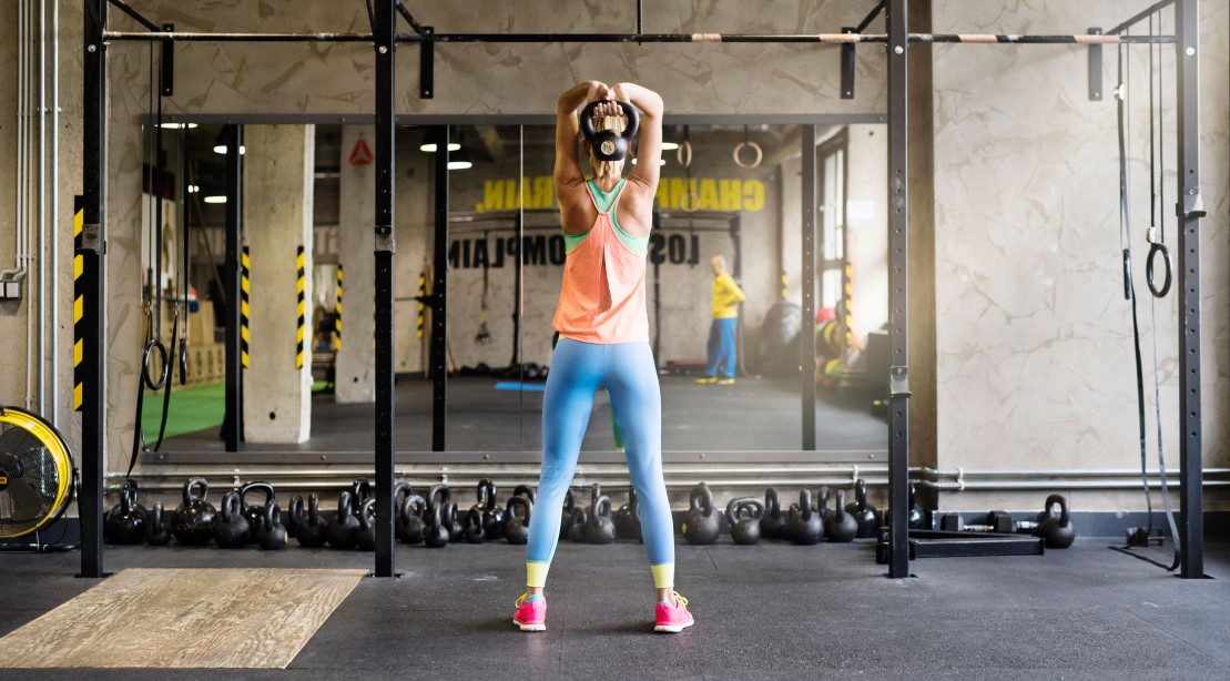 Woman in Gym Lifting Kettlebell
