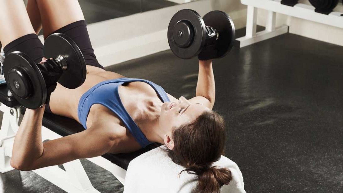 woman lifting weight from a prone position