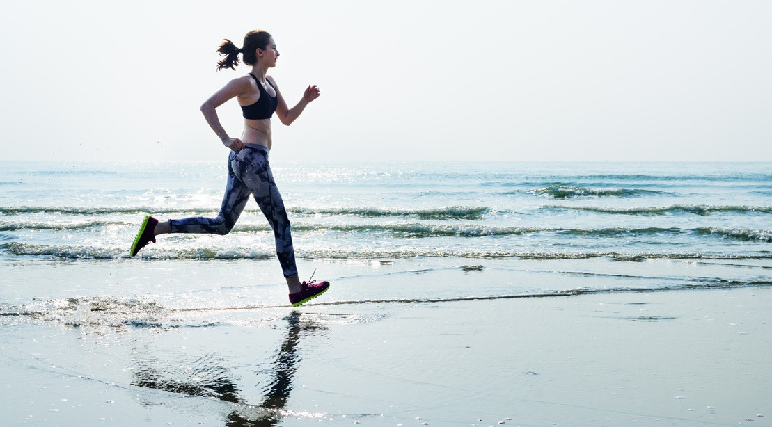Woman Running In The Sand Next To The Ocean