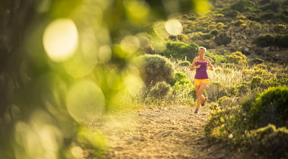 Woman Trail Running Outdoors In Tank and Shorts