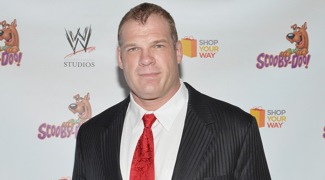 WWE Wrestler Kane Poses On The Red Carpet In A Suit And Tie.