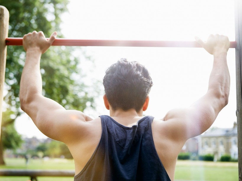 Man doing pullups outdoors in park