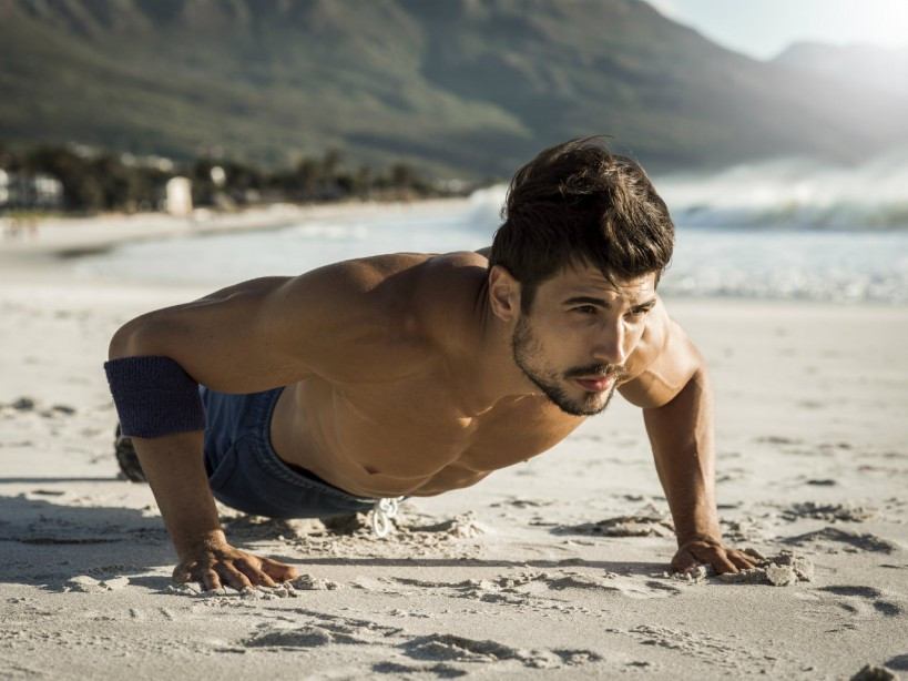 Man doing pushups on the beach