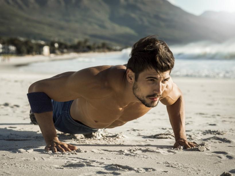 Man doing pushups on the beach