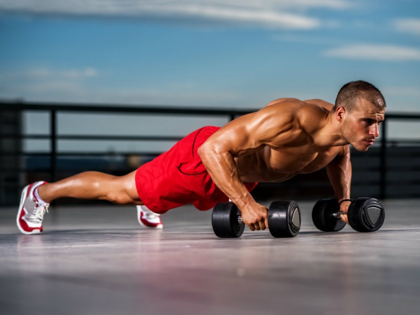 Man doing pushups with dumbbells