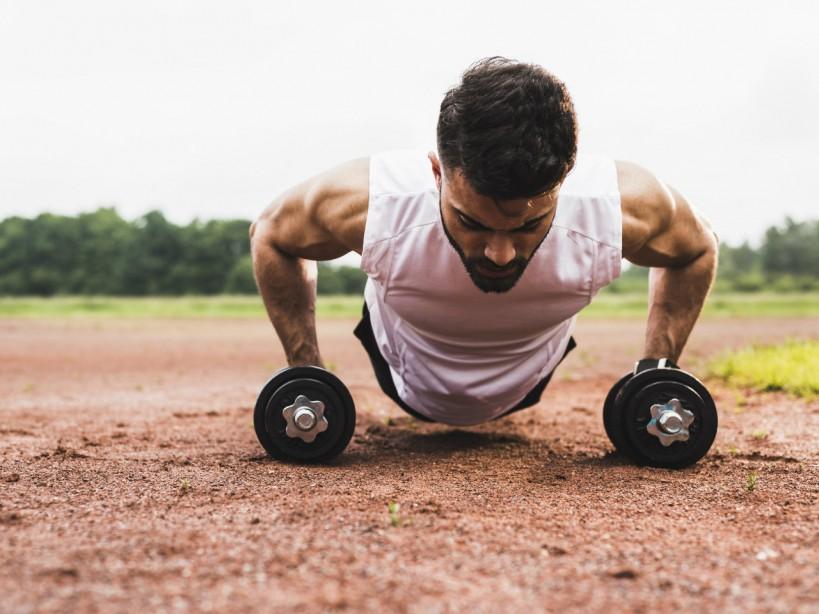 Man performing pushups on dumbbells