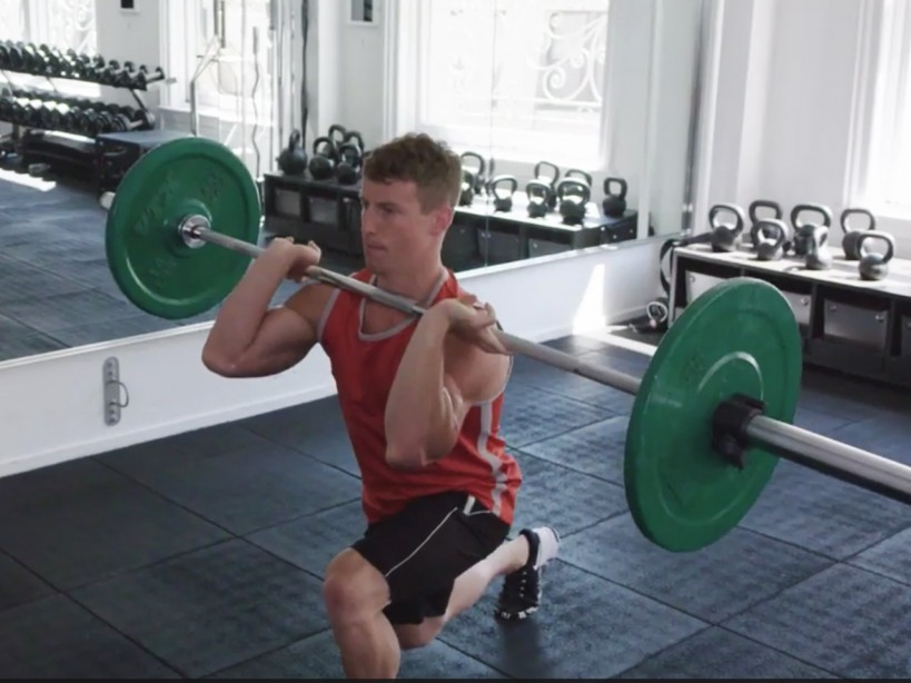 Man does reverse lunge with barbell