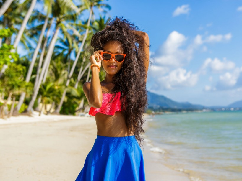 Young woman on beach wearing sunglasses