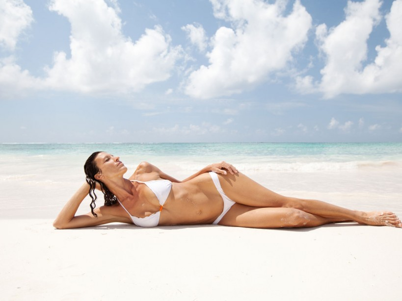 Woman posing in white bikini on beach