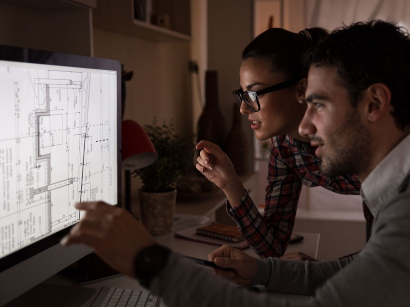 Young, attractive couple working late in office