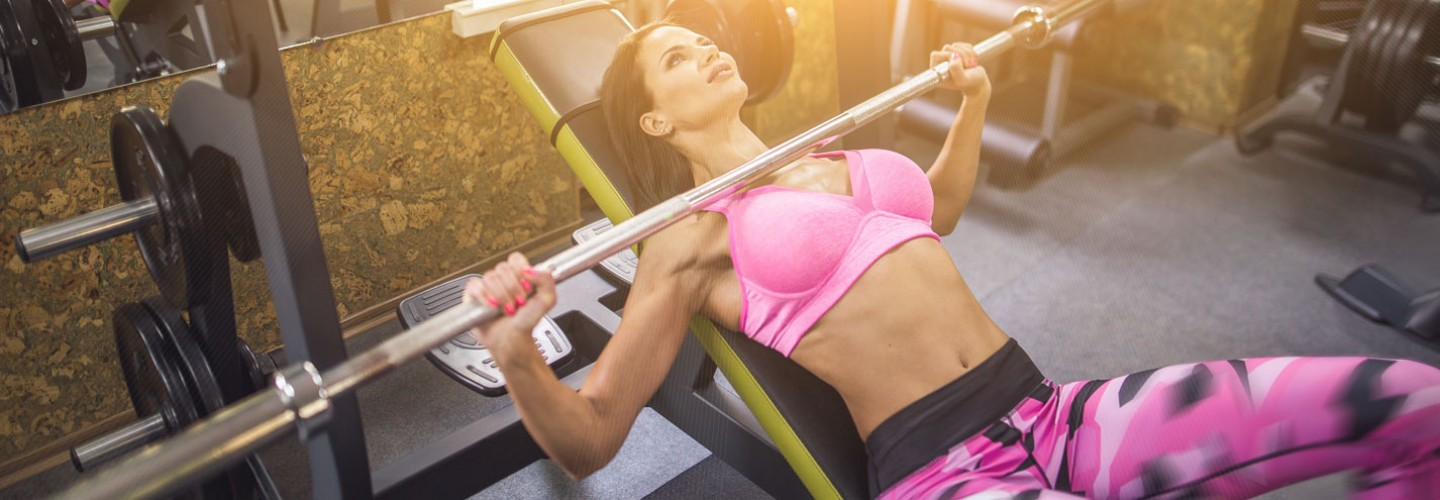 Woman doing incline barbell bench press in pink workout attire thumbnail